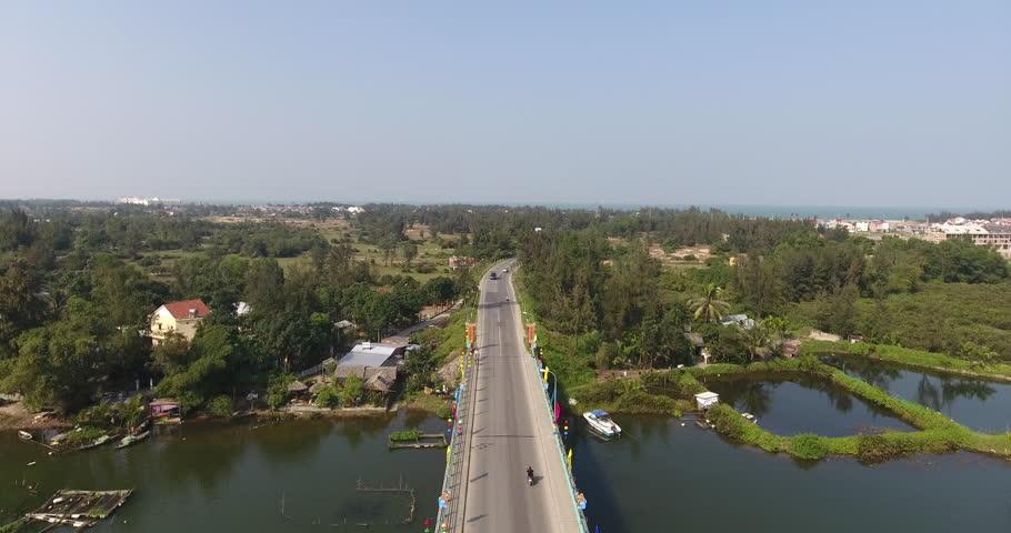 Aerial view following traffic crossing over a bridge in Hoi An, Vietnam. | Shutterstock HD Video #1018930165