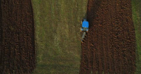 Top view of the tractor that plows the field. Aerial view of a tractor plowing field.
