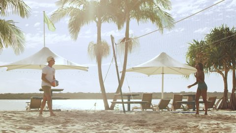 Young couple on vacation playing beach volleyball with ocean, palm trees and in umbrellas in the background in Australia. Wide shot on 4k RED camera.
