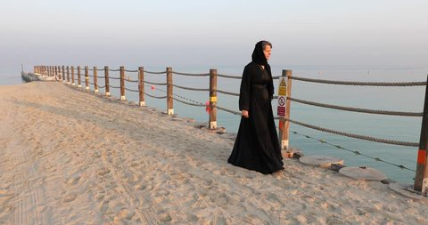 Beautiful middle aged woman in a traditional black abaya walking on the sandy beach on a jetty in Dubai during early morning hours. Dubai, UAE.