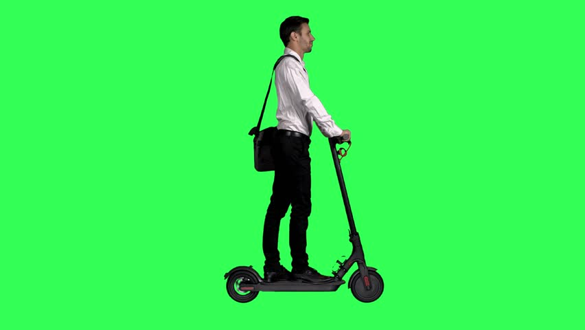 Riding an electric scooter to work by a young businessman over a green screen,