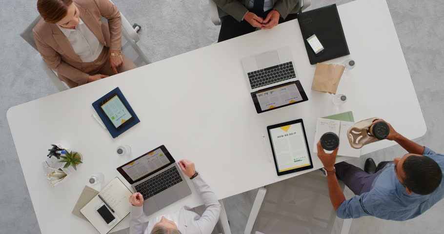 multi ethnic business team using tablet pc technology in boardroom meeting browsing corporate research statistics brainstorming creative ideas colleague sharing coffee #1019015005