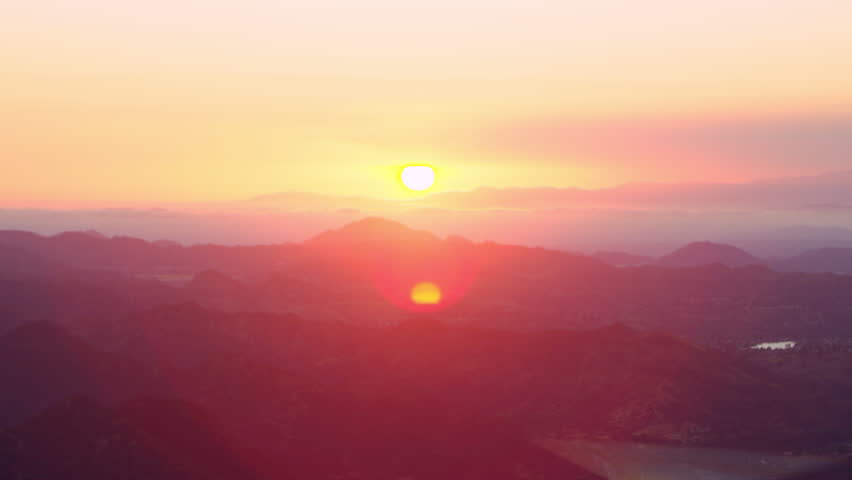 Aerial view of helicopter flying over mountain range during gorgeous pink sunset in Los Angeles, California. Wide long shot on 4K RED camera. #1019022325