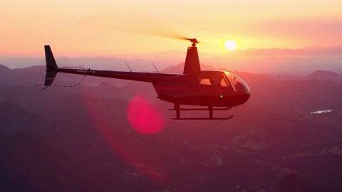 Aerial view of helicopter flying over mountain range during gorgeous pink sunset in Los Angeles, California. Wide long shot on 4K RED camera.
