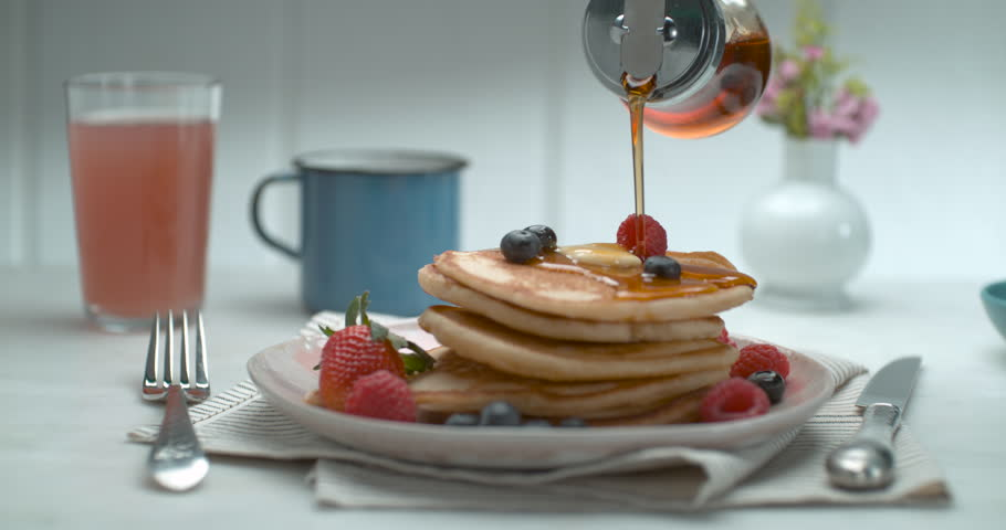 Maple syrup is poured over a stack of pancakes with fruit and butter on a table with a background in soft focus, in slow motion, in soft light. Closeup shot in 4K on a Phantom Flex | Shutterstock HD Video #1019032645