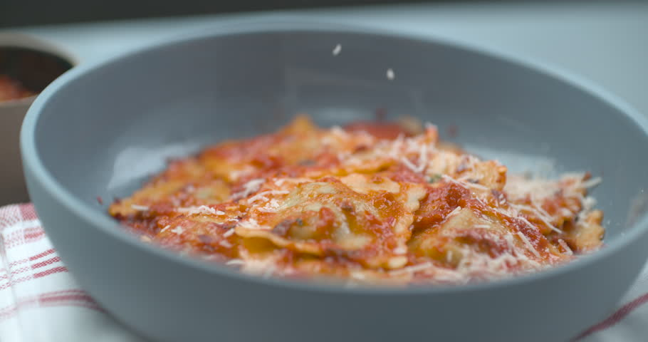 Parmesan cheese being grated onto tomato ravioli dish in bowl in ultra slow motion with 4k Phantom Flex camera