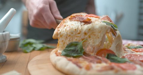 Freshly baked wood fired pizza being sliced with melty cheesy closeup ultra slow motion with 4k Phantom Flex camera