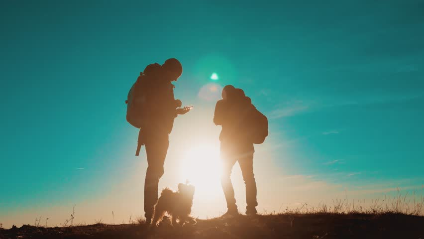 Teamwork smartphone navigation. two tourists hikers men with backpacks at sunset go hiking trip. hikers adventure and the dog go walking. travel mountains silhouette. lifestyle hikers adventure and | Shutterstock HD Video #1019041765