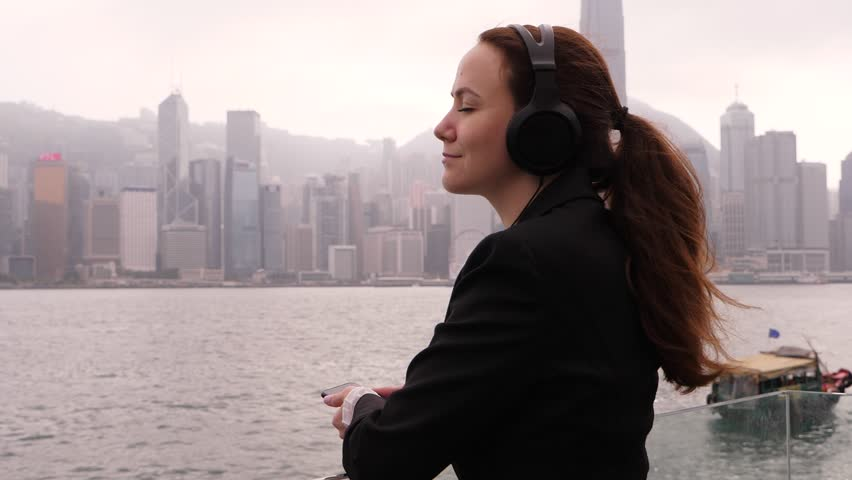 Woman in black suit rest at city embankment, listen music, stay with eyes closed against Victoria Harbour. Hong Kong island buildings seen on background #1019093785
