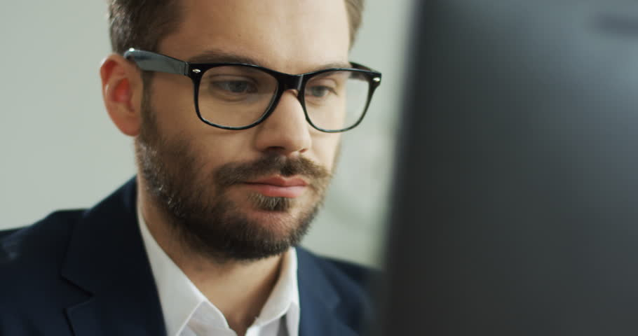 Close up of the Caucasian good looking young man in glasses with serious face working at the computer. Portrait. Inside. | Shutterstock HD Video #1019094385