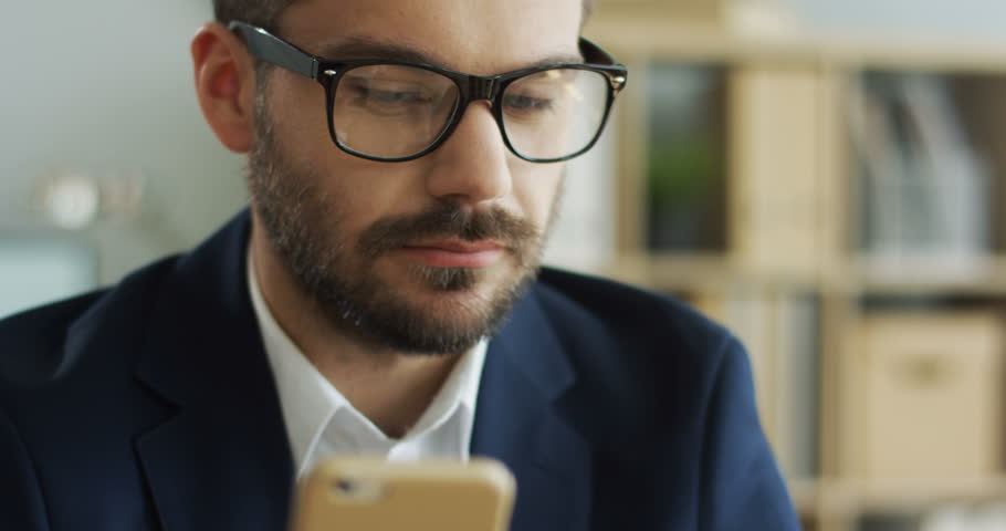 Close up of the young Caucasian man in business style and glasses shopping online on the smartphone with a credit card and being happy. Portrait. Inside. | Shutterstock HD Video #1019094445