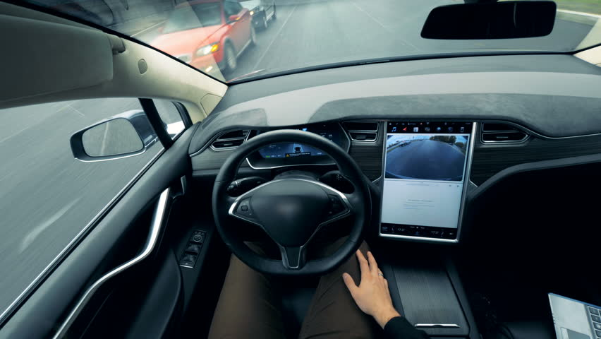 Person controls a self-driving car. Autonomous autopilot driverless car