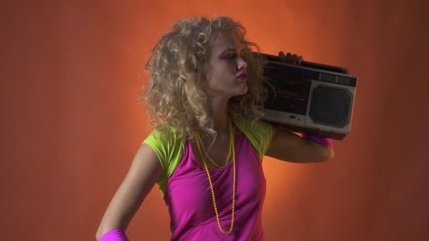 Blonde woman in 80s clothes with boombox on her shoulder enjoying the music