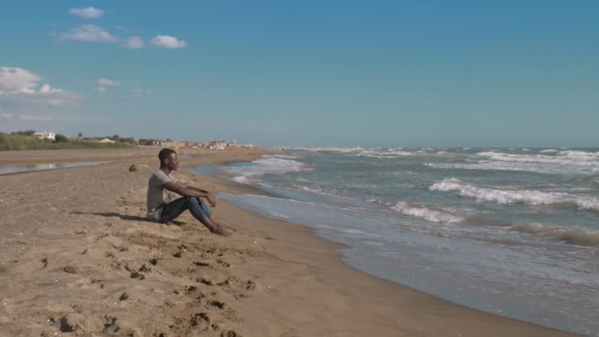 Thoughtful black american young man sitting on the beach. Thoughts,dreaming | Shutterstock HD Video #1019144215