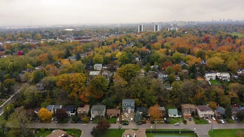 Aerial shot of city park and suburban neighbourhood at Scarborough Bluffs during peak fall colors.