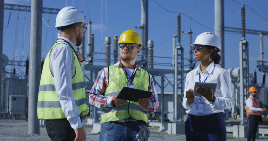 Medium shot of three electrical workers reviewing documents on a tablet during an inspection against the background of a transformer station #1019245705