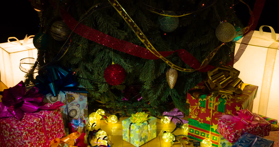Christmas Gifts for the whole Family. The camera slowly goes down under the decorated Christmas tree under which there are gifts in colorful boxes