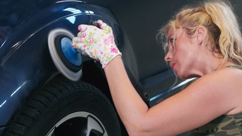Young woman worker polishing car body at service. Woman worker waxing car with polisher. Car care work in auto service