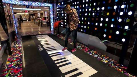 New York City, USA - September 6, 2018: Buyers having fun with big floor piano in Macys store at Manhattan