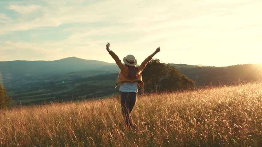 Happy young woman with hat walking in field touching wheat ears at sunset lifts his hands up smiling countryside nature summer girl sunshine freedom agriculture close up portrait slow motion #1019389435