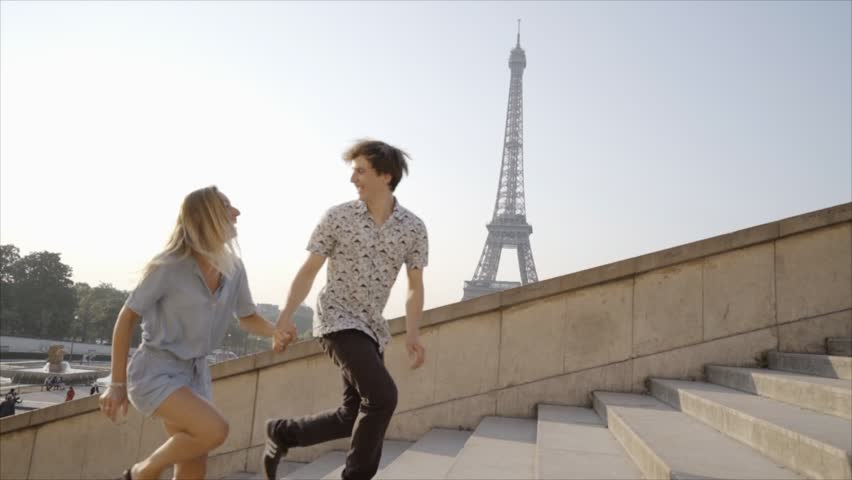Young couple having fun running up the stairs at the Tour Eiffel in Paris, France. Two people laughing, boyfriend holding girlfriends hand pulling her up. City trip vacations  | Shutterstock HD Video #1019433625
