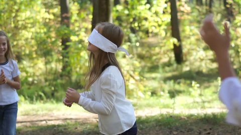 Kids playing blind man's buff at the park. Girls having fun together outdoors