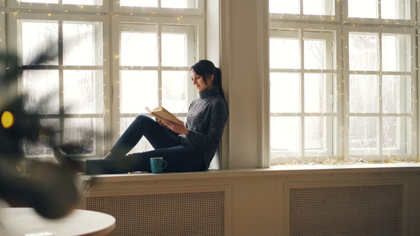 Relaxed girl is reading book on Christmas day sitting on window-sill and looking out of window in December wearing sweater and jeans. Hobby, holiday and youth concept. | Shutterstock HD Video #1019476765