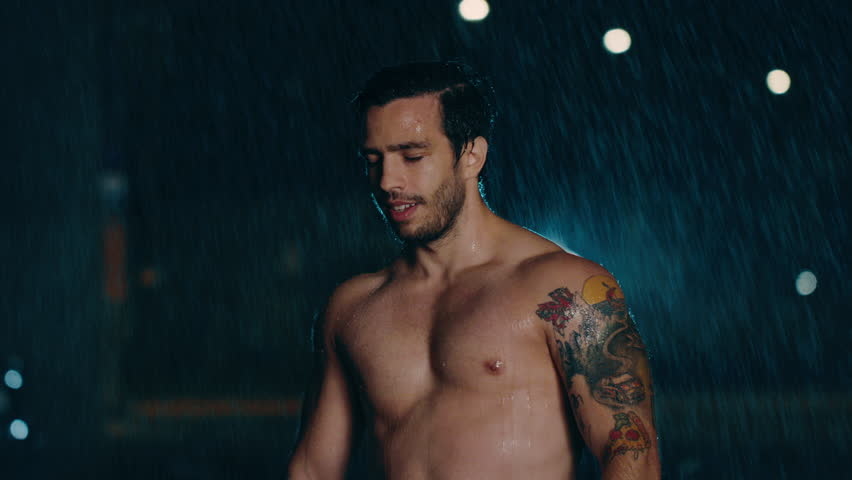 Shirtless Athletic Muscular Young Man is Celebrating His Sport Accomplishments on a Rainy Night. He is in an Urban Environment Under a Brindge with Cars in the Background.