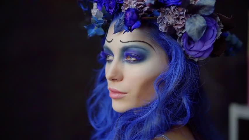 Portrait of beautiful woman wearing fantastic makeup for halloween, beautiful flowers in a blue hair. | Shutterstock HD Video #1019508835