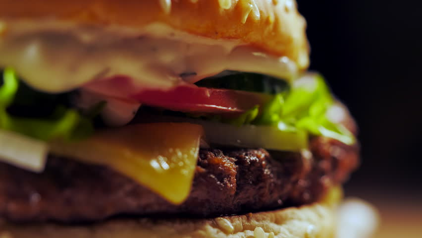 Big appetizing burger with meat cutlet, onion, vegetables, melted cheese, lettuce and mayonnaise sauce. Isolated hamburger rotates on dark smoke background, close-up view | Shutterstock HD Video #1019552995