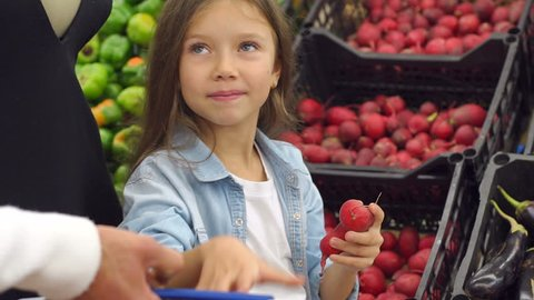 Close-up of a little girl puts in a grocery basket fresh radish, a girl buys vegetables with their parents in the supermarket. Portrait. Slow motion. Family at the grocery store.