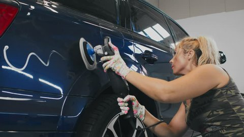 Blonde woman polishing car body at auto service. Woman worker waxing car after washing body. Car body work in auto service
