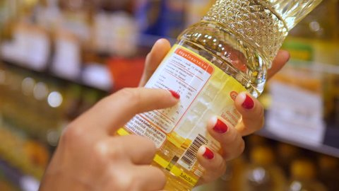 Woman Customer Reading Label On Sunflower Oil At Supermarket.