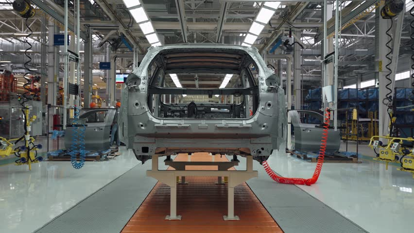 BELARUS, BORISOV - OCTOBER 19, 2017: Automobile plant, modern production of cars, car body assembly process, workers serve cars, automated production line. Timelapse.
