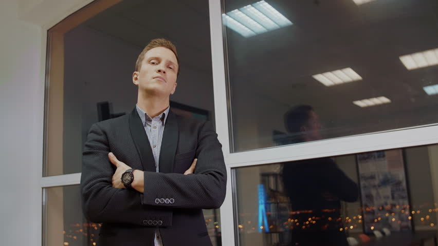 Successful businessman in classical formal suit standing in evening office with hands crossed on chest near window, looking at camera, ready for new projects, challenges. | Shutterstock HD Video #1019695465