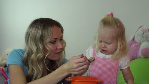 child refuses to eat porridge. Mom is trying to feed her daughter porridge.
