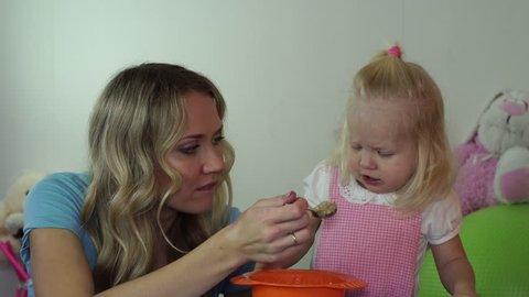 child refuses to eat porridge. Mom is trying to feed her daughter porridge.