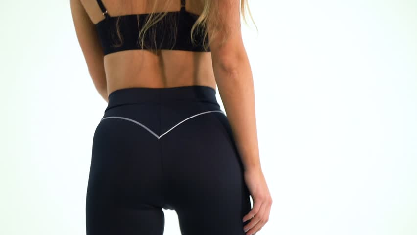 04f1bafee8 Woman with the nice figure in yoga pants posing in the studio, close up,  slow motion
