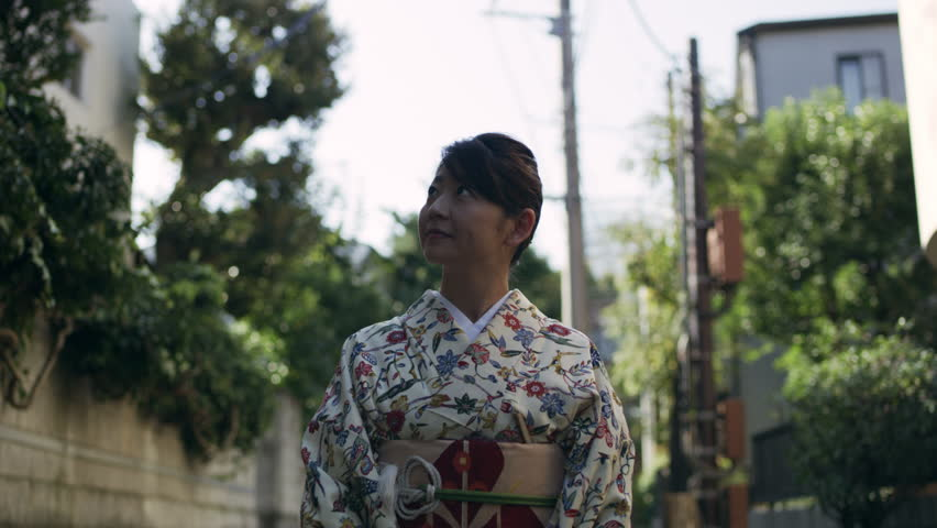 Smiling female wearing traditional floral kimono walking down a quiet residential street in Japan, with soft day lighting. Medium shot on 4k RED camera.