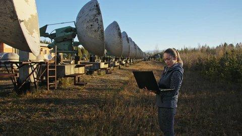 Woman student operator of institute of Solar Terrestrial Physics monitors communication equipment in notebook. Unique array solar radio telescope. Sun Solar Radio Telescope. The 'Quasar' observatory