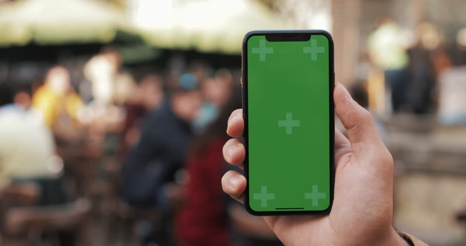 Closeup of a man's hand holding a mobile telephone with a vertical green screen on the streets. Tourist tram goes in the background #1019988295