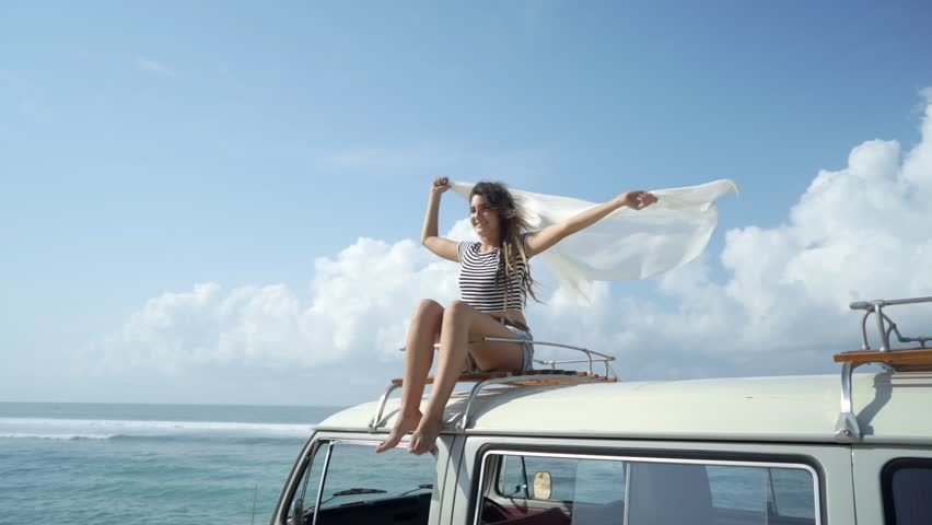 Beautiful woman travel by car and enjoy road trip nature sitting on the roof at summer day #1019992855