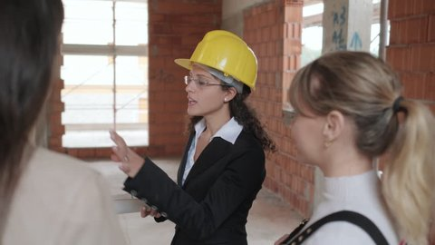 Architect talking with clients in building. Woman working as engineer in construction site with customers. Project supervisor showing home to lesbian couple.