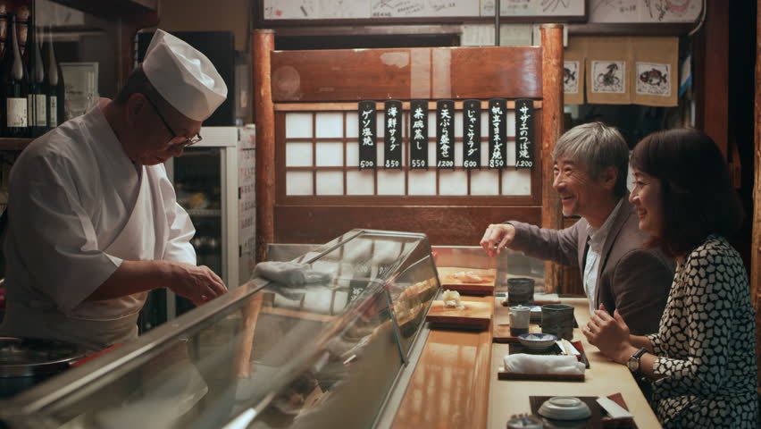 Happy Japanese couple eating sushi while watching and talking to chef in small sushi bar with soft interior lighting. Close up shot on 4k RED camera. | Shutterstock HD Video #1020054475