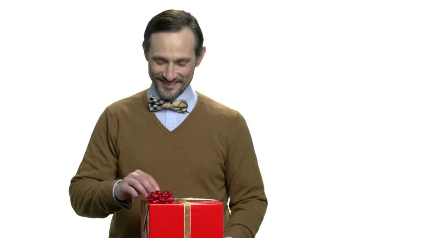 Handsome man showing red gift box. Middle-aged guy presenting gift box. Special offer concept.   Shutterstock HD Video #1020084535