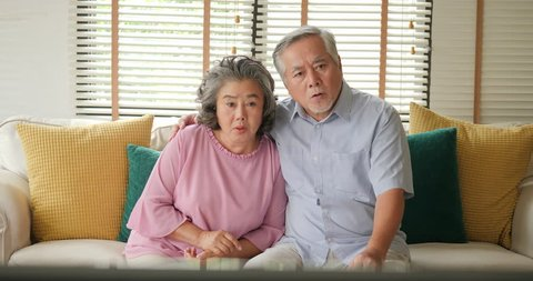 Asian senior couple watching television movie with excite emotion together in living room. People with relaxation, old age, retirement, senior lifestyle family concept.