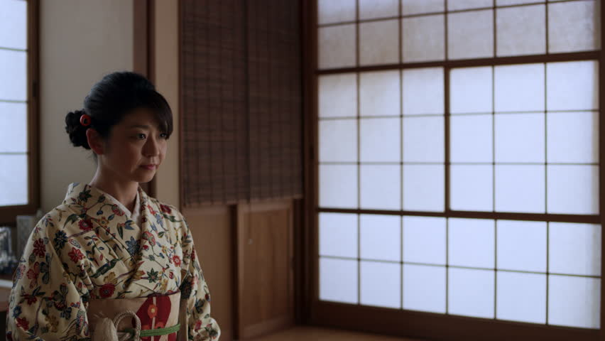 Female wearing a kimono is sitting in a room ready for a tea ceremony in a traditional Japanese home with soft day lighting. Medium shot on 4k RED camera. | Shutterstock HD Video #1020112465