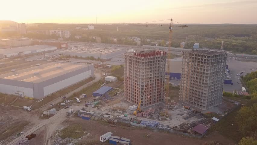 Construction site in sunset light, two new building and crane aerial video