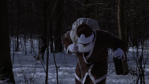 Drunk Santa Claus with a bottle of alcohol in the winter in the woods at night. Video footage of drunk Santa Claus with a bottle of alcohol in the winter in the woods at night.