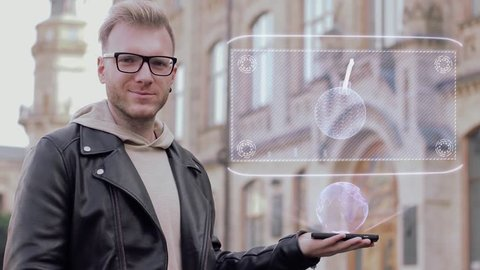 Smart young man with glasses shows a conceptual hologram bomb. Student in casual clothes with future technology mobile screen on university background